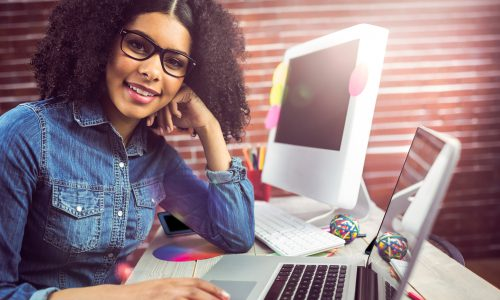 Portrait of casual female designer using laptop at workplace